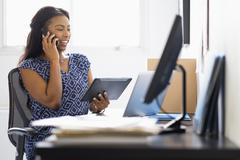 Mixed race woman multitasking in office Stock Photos