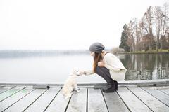 Japanese woman petting dog near lake - stock photo
