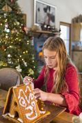 Caucasian girl decorating gingerbread house Stock Photos