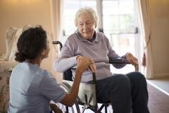 Nurse talking to patient in wheelchair Stock Photos