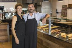 Caucasian business owners smiling in cafe - stock photo
