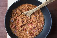 Vegan quinoa Sloppy Joe sauce in a cooking pot with wooden spoon Stock Photos