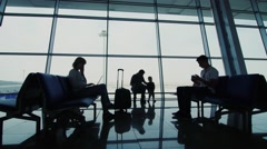 A family of four people waiting for a flight at the airport terminal - stock footage