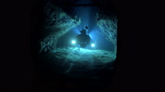 Scuba diver swims inside the wreck tunnel at night - Cousteau's precontinent  Stock Footage