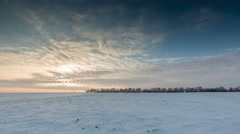 Timelapse. The movement of the clouds at sunset in the snowy steppe in winter. Stock Footage