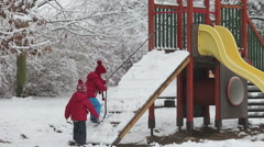 Young preschool children, climbing on a slide on playground, wintertime Stock Footage