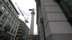 View of a tower crane and The Monument to the Great Fire of London in London - stock footage