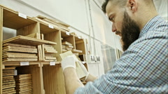 Bearded painter puts the oil-paint on a copy of the board for the selection of - stock footage