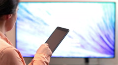 Woman watches television while holding a tablet device Stock Footage