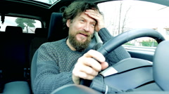 Man with long beard and hair almost crying while driving car slow motion Stock Footage