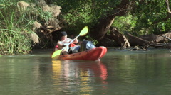 Three canoes rowing along bend in river. - stock footage