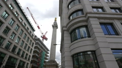 Tower crane seen near The Monument to the Great Fire of London in London Stock Footage