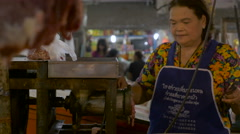 A Thai woman grinds fresh meat in a traditional market in Asia Stock Footage