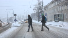 Citizen people and automobiles under snowstorm on city center street. 4K - stock footage
