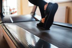 Treadmill used by sportswoman for running in gym Stock Photos