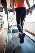 Attractive sportswoman running on treadmill in gym Stock Photos