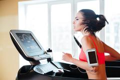 Woman running on treadmill in gym and listening to music Stock Photos