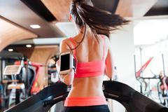 Woman athlete with balnk screen smartphone running on treadmill Stock Photos
