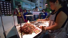 An unidentified woman sells street exotic food Stock Footage