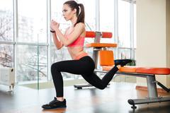 Sportswoman doing squats using bench in gym Kuvituskuvat