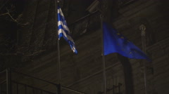 Two flags waving on the pole at night Stock Footage