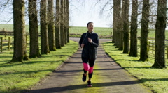 4K Young woman running in the countryside stops to get her breath back - stock footage