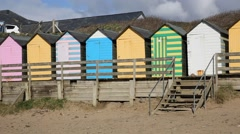 Pan view of numerous colourful English beach huts traditional English structure Stock Footage