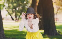 Sexual woman in hat, beckoning gesture, outdoors - stock photo