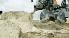 The clamp of the backhoe getting few limestones Stock Footage