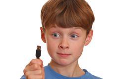Irritated boy looks at a USB jack - stock photo