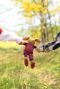 Close up of a toy rabbit kept in the hands of two children Stock Photos