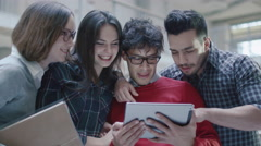 Group of young multi-ethnic students are using a tablet computer in a college - stock footage