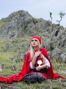Beautiful blonde woman in old-fashioned dress and red cloak sitting on the ro Stock Photos