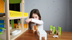 A cute girl playing with her dollhouse Stock Footage