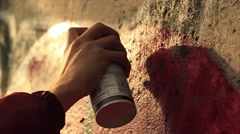 Guy doing street art graffiti with aerosol in action close Stock Footage