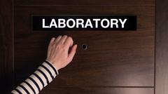 Woman knocking on laboratory door Stock Footage
