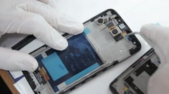 Mobile phone repair lab technician at work Stock Footage