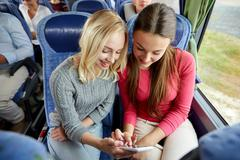 Happy young women in travel bus with smartphone Stock Photos