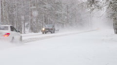 Cars move along the snow-covered road in the snow Stock Footage