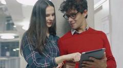 Caucasian girl and a hispanic male students use a tablet computer in a college Stock Footage