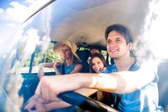 Hipster boy driving an old campervan with teenagers, roadtrip Stock Photos