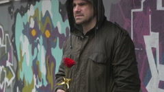 Sad man with wet jacket holding red rose and waiting woman on downpour, tilt up. Stock Footage