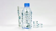 Glass with ice water and the plastic bottle close up loopable rotation. - stock footage