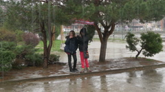 Two young girls standing under umbrella, talking and waiting to stop downpour. - stock footage