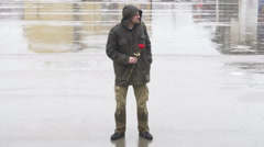 Guy holding red rose,waiting girl on rain,reads message and leaves disappointed. Stock Footage