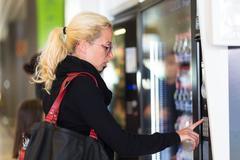 Lady using  a modern vending machine Stock Photos