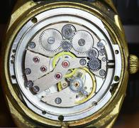 old watch mechanism with moving pendulum - stock photo