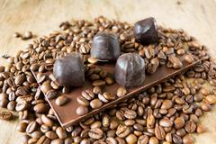 Tiles of dark chocolate candy coffee beans - stock photo