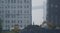 Heavy excavator picking up mud at construction site Stock Footage