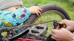 Father and Son, 1 year old boy, are spending quality time together fixing a bike Stock Footage